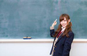 黒板の前でチョークを持っている女子中学生