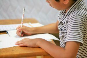 一生懸命、机で勉強に取り組んでいる男の子