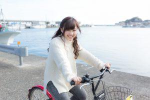 海が見える場所で、自転車をこいでいる女性