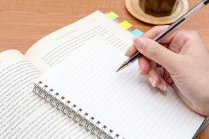 テキストの大切な箇所をノートにメモしながら勉強中