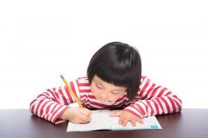 机で一生懸命に勉強に取り組んでいる女の子