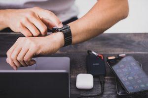 自分の腕時計を確認している男性
