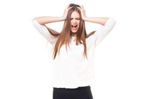 テストでケアレスミスをして、後悔して頭を抱えている女性