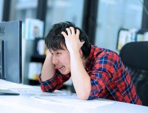 ケアレスミスで失敗して、机の上で頭を抱えている男性