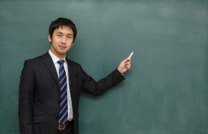 黒板の前で授業している塾講師