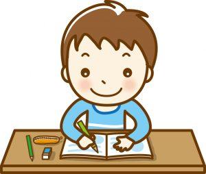机に向かって、勉強に取り組む男の子