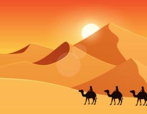 砂漠をラクダで移動する人々