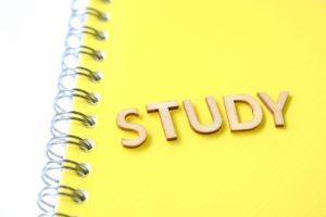 studyという文字が載っている黄色いノートの写真