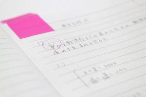 付箋が貼られていて連立方程式の計算が書かれているノートの写真